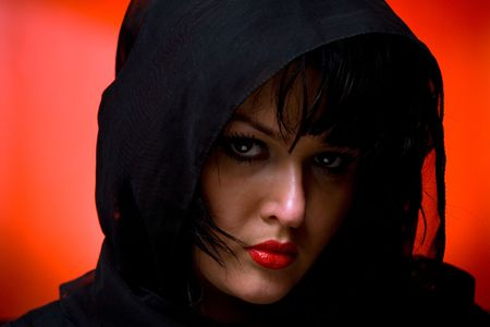 witch face: Portrait of young nice woman in black veil on red back
