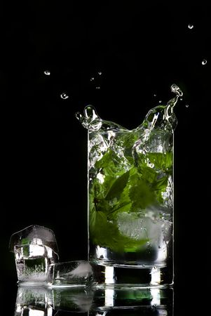 View of glass filled with green tea and ice cubes aside Stock Photo