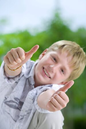 Portrait of young boy giving his thumbs up photo