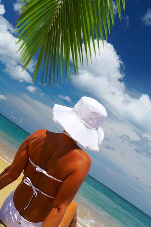 singleness: view of nice woman lounging on tropical beach in white panama and bikini