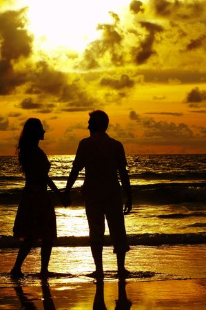 crepuscular: view of young couple walking along the shore during sunset