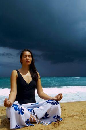 solter�a: vista de mujer joven agradable practicando yoga en la playa de tormenta