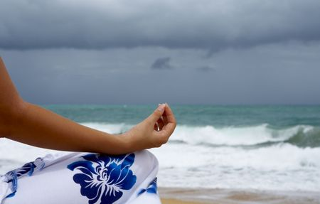 singleness: View of woman�s hand during yoga meditation on stormy beach