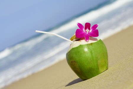 coconut drink: view of nice fresh tropic cocktail decorated with orchid on sandy beach