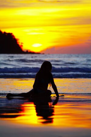 view of a girl lounging on tropical beach during sunset Stock Photo