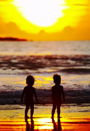 brood: view of two kid's silhouettes   on the beach during sunset