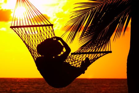 laze: view of a woman lounging in hammock during sunset