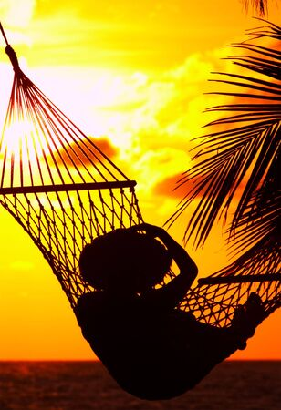 plage: view of a woman lounging in hammock during sunset