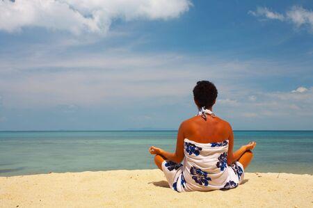 solter�a: vista de una mujer meditando en la playa temprano en la ma�ana Foto de archivo