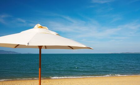 solter�a: agradable vista de blanco lienzo sombrilla en la playa Foto de archivo