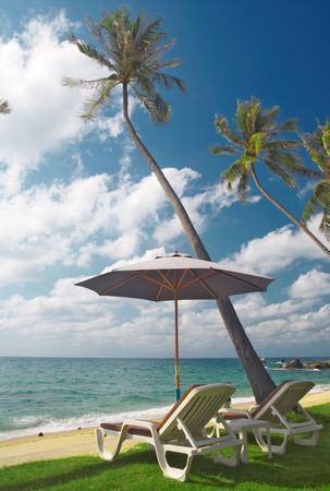 singleness: view of two chairs and  white umbrella on the beach  in the morning Stock Photo
