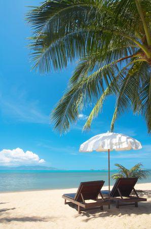 solter�a: vista de dos sillas y sombrilla blanca en la playa
