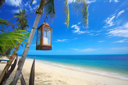 view of old lantern hanging in tropical environment photo