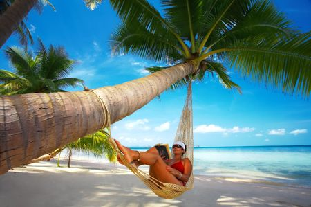 palm reading: view of nice woman reading a book in hammock in tropical environment Stock Photo