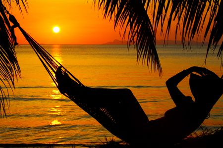 view of a woman lounging in hammock during sunset photo