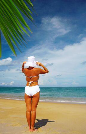 singleness: view of nice woman in white panama and bikini on tropical beach Stock Photo