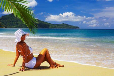 solter�a: bonita vista de la mujer en la playa tropical lounging en bikini blanco y Panam� Foto de archivo