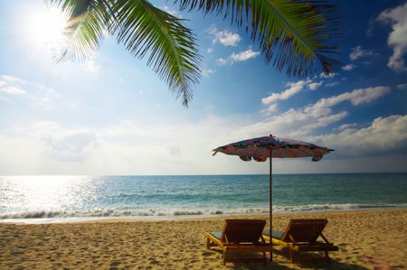singleness: view of two bamboo chase lounges and  umbrella on the beach