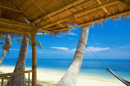 shanty: view of nice tropic beach and exotic palm roof Stock Photo
