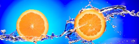 Close up view of two sliced orange pieces getting splashed with water photo