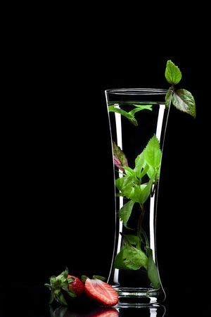 View of long glass filled with fresh drink on black back photo