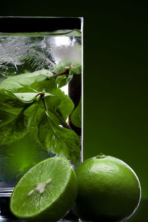 View of glass filled with green tea and some limes nearby photo