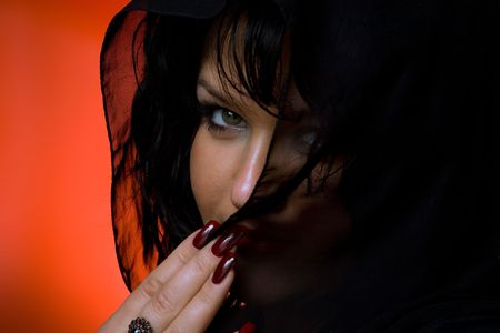 Portrait of young nice woman in black veil on red back photo