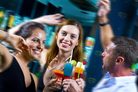 Motioned portrait of young attractive people having fun in night club photo