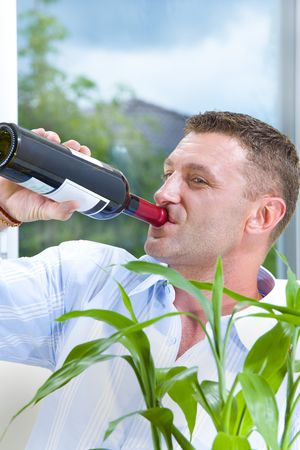 careless: Portrait of young man drinking straight from the bottle