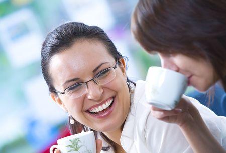 Portrait of young pretty women having coffee break in office environment photo