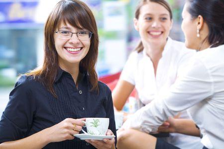 breakfast table: Portrait of young pretty women having coffee break in office environment