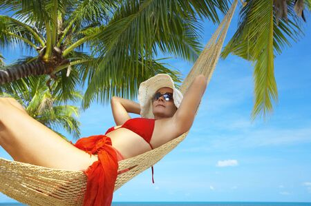 hummock: view of nice woman lounging in hammock in tropical environment