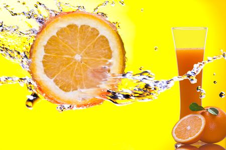 View of piece of orange getting splashed  and  glass of juice on back photo