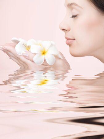 olfato: Retrato de joven mujer hermosa sobre fondo de color rosa