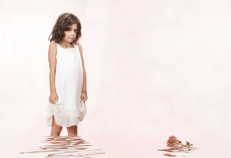 Studio portrait of  nice little girl getting through the water photo