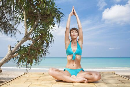 Portrait of young woman practicing yoga in summer environment photo