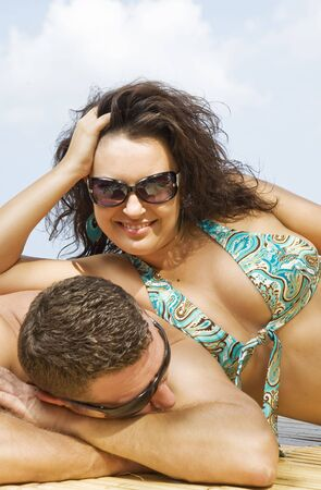giggle: a portrait of attractive couple having fun on the beach.