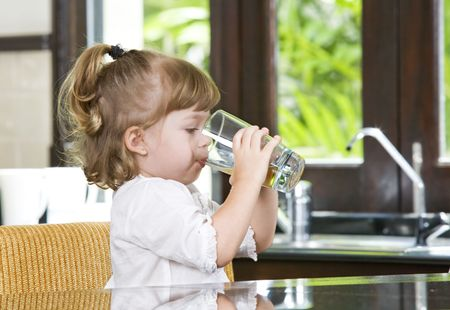 girl drinking water: Portrait of little girl having drink in domestic environment