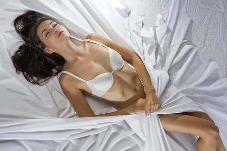 sleepiness: Portrait of young beautiful woman on white sheet