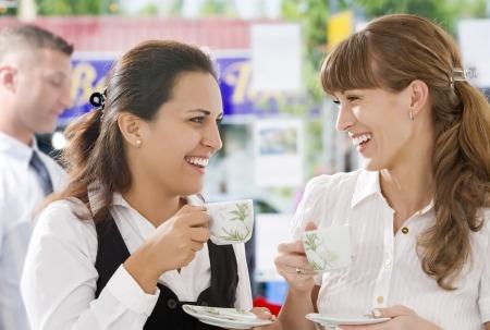 having a break: Portrait of young pretty women having coffee break in office environment