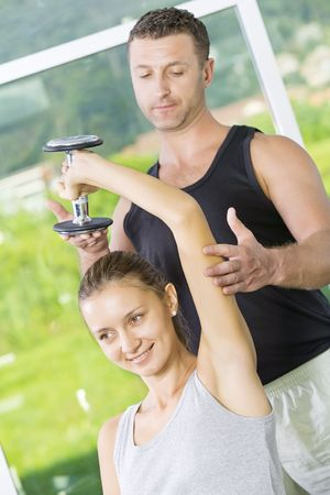 Portrait of young nice couple getting busy in gym     photo
