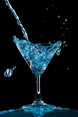 sweet vermouth: View of glass with Blue Curacao splash on black background