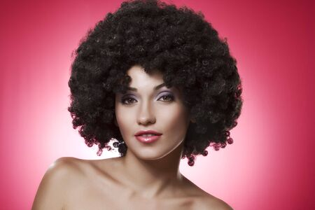 Close up portrait of young woman in afro wig on pink  back Stock Photo - 5828175