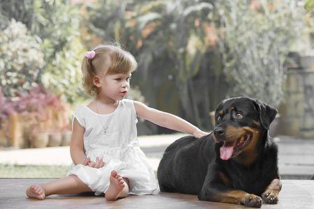 rottweiler: Portrait of little girl having good time  in summer environment