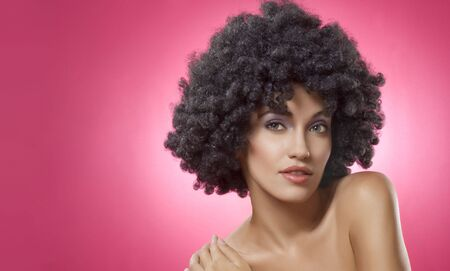 Close up portrait of young woman in afro wig on pink  back photo