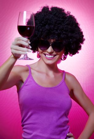 Portrait of young nice woman with glass of wine on pink back photo
