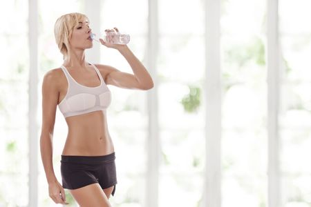 Portrait of nice young woman drinking water in summer environment