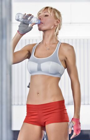 Portrait of nice young woman drinking water in gym photo