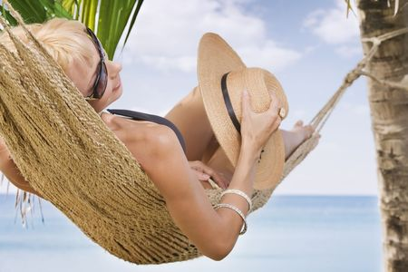 hammock beach: view of nice woman lounging in hammock in tropical environment