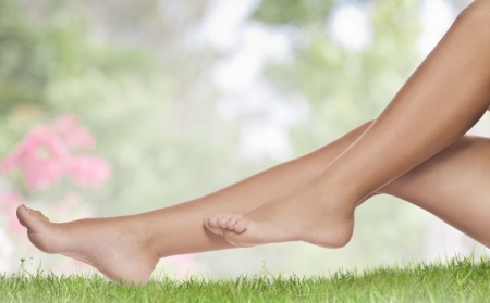 close up view of smooth woman�s legs on color background photo